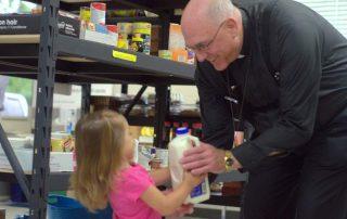 Archbishop Joseph Naumann giving milk to young girl