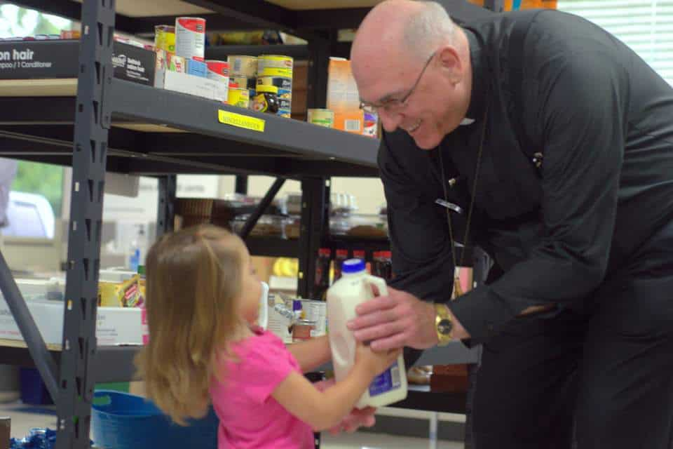 Archbishop Joseph Naumann giving milk to young girl