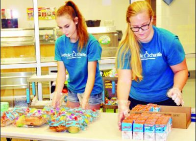 Kortnee VanDonge (left) and Cali VanAusdall (right) are two of several Holton High School students who are volunteering to serve free lunches to children at the Holton Elementary School each Monday through Friday in June. Through Catholic Charities of Northeast Kansas two free lunch sites have been set up in Holton so children don't go hungry through the summer months. (Photo by Ali Holcomb)
