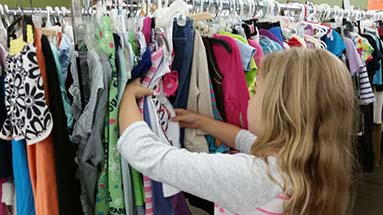 girl looking at kids clothes