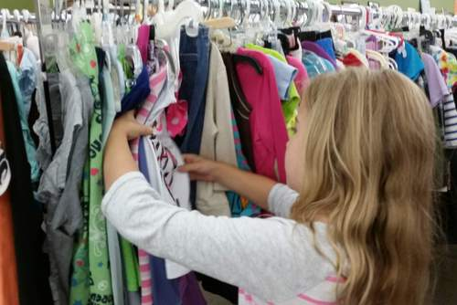 Girl looking at kids clothes at TurnStyles Thrift Store