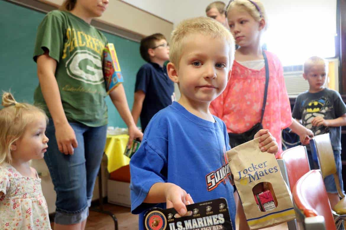 Children receiving food from the Kids Summer Food program - header image with boy in blue shirt